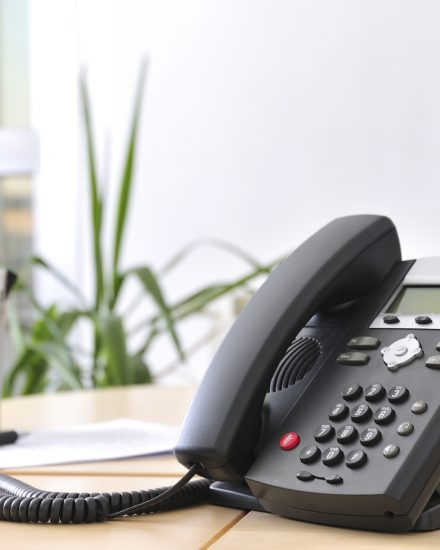 Executive VoIP phone on a beech desk